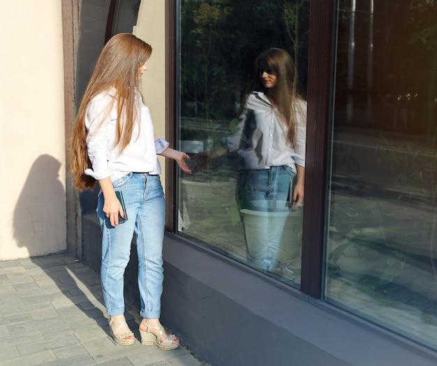 Junge frau mit langen haaren steht neben ihrem spiegelbild in einer glasvitrine und berührt ihre hand