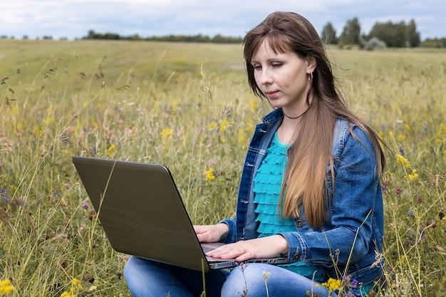 Junge frau mit laptop, der auf grünem gras sitzt. mädchen mit einem laptop in der natur.