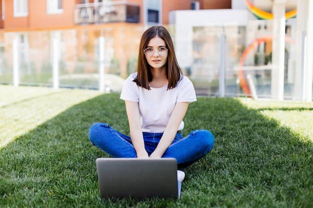 Junge frau mit laptop, der auf grünem gras sitzt und auf eine anzeige im freien schaut