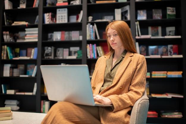 Junge frau mit laptop, die auf dem bildschirm durch ebook schaut