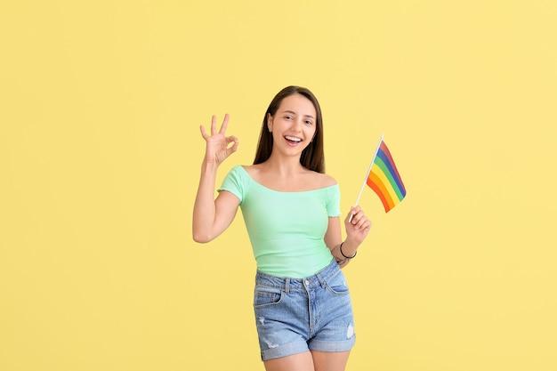 Junge frau mit lgbt-flagge zeigt ok auf gelb