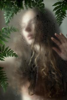Junge frau mit locken hinter nassem glas mit grünen blättern