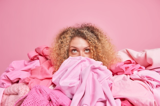 Junge frau mit lockigem haar, die sich oben konzentriert, bringt die dinge in ordnung, umgeben von einem kleiderstapel sammelt kleidungsstücke, die über rosa wand isoliert sind. horizontale monochrome aufnahme. bekleidungsrevisionskonzept