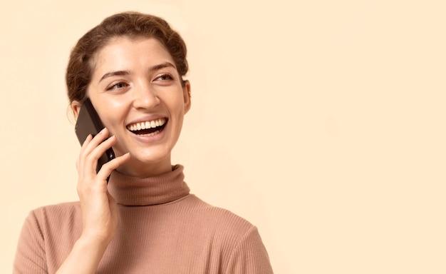 Junge frau mit lockigem haar unter verwendung des mobiltelefons