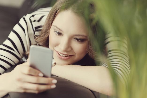 Junge frau mit lockigem haar unter verwendung ihres smartphones