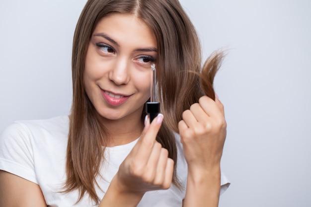 Junge frau mit luxuriösem haar wendet conditioner für haarpflege an