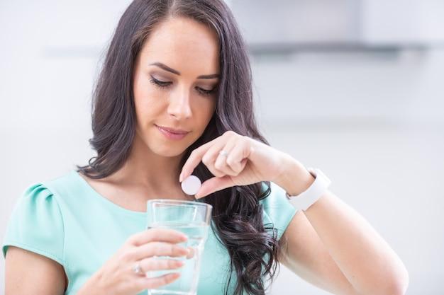 Junge frau mit magnesia-brausetablette und glas reinem oder mineralwasser