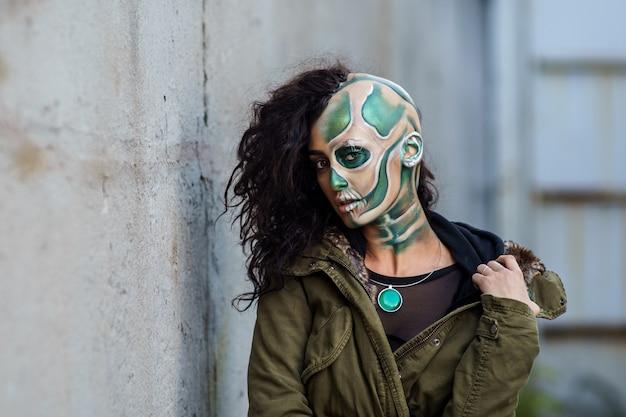 Junge frau mit make-up des grünen schädels für halloween.