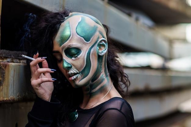 Junge frau mit make-up des grünen schädels für rauchende zigarette halloweens.