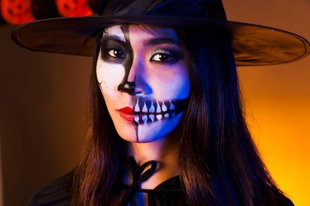 Junge frau mit make-up und gruselige maske