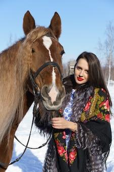 Junge frau mit make-up und rotem lippenstift mit einem pferd im winter an einem sonnigen tag gegen den himmel