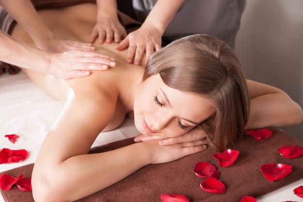 Junge frau mit massage im beauty spa von zwei therapeuten