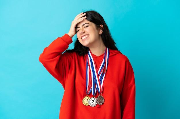 Junge frau mit medaillen auf weißer wand isoliert hat etwas erkannt und beabsichtigt die lösung