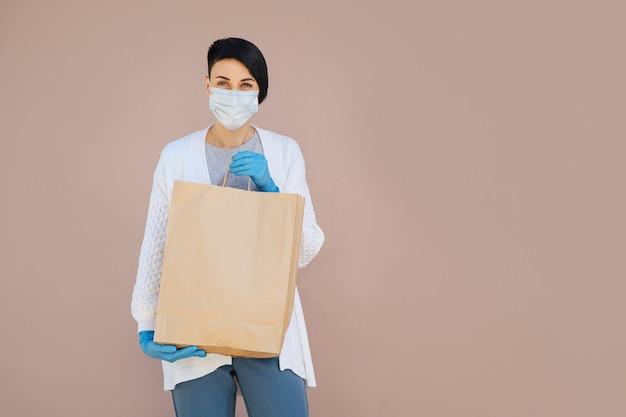 Junge frau mit medizinischer einwegmaske, die während covid 19 einkäufe liefert