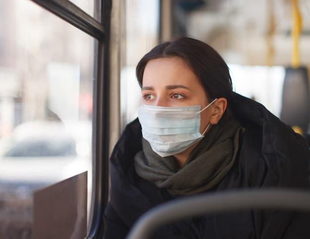 Junge frau mit medizinischer maske im stadttransport, im bus, in der herbstkleidung
