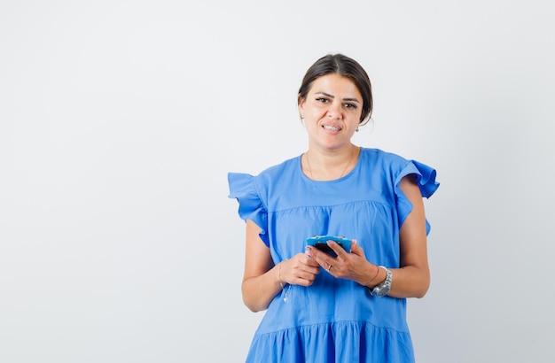 Junge frau mit mini-klemmbrett im blauen kleid und hübsch aussehend