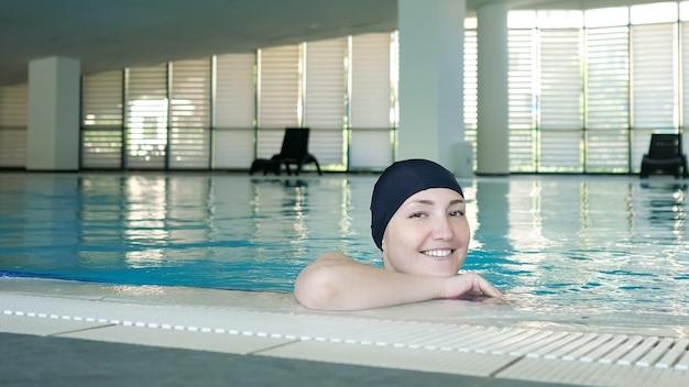 Junge frau mit mütze im schwimmbad