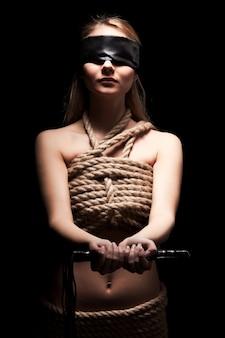 Junge frau mit nacktem körper bedeckt mit seilen und augen geschlossen mit schwarzem lappen, der lederpeitsche in den händen im dunklen raum hält. sexuelle spiele und praktizierendes bdsm-konzept