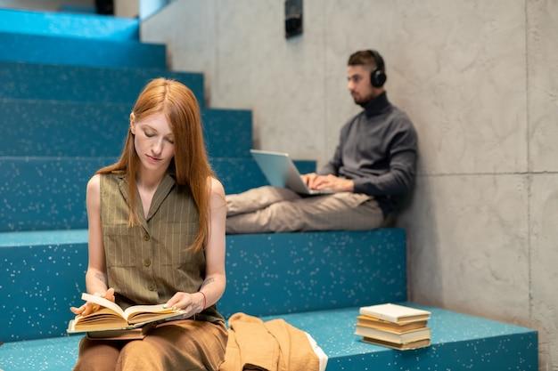 Junge frau mit offenem buch liest roman, während sie auf der stufe der blauen treppe sitzt