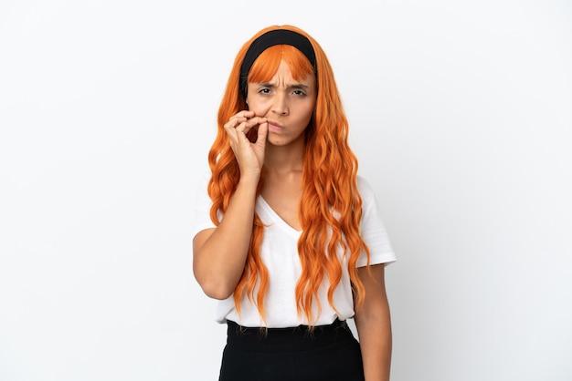 Junge frau mit orangefarbenem haar auf weißem hintergrund, die ein zeichen der stille zeigt