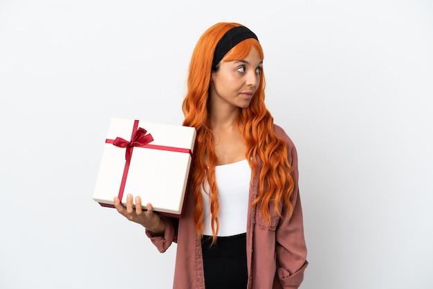 Junge frau mit orangefarbenem haar, die ein geschenk auf weißem hintergrund hält und zur seite schaut
