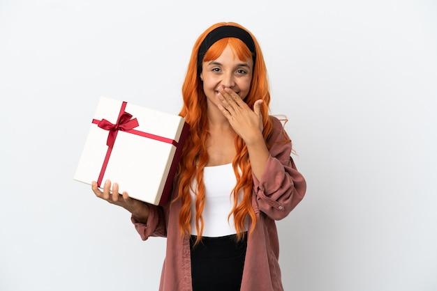 Junge frau mit orangefarbenem haar, die ein geschenk isoliert auf weißem hintergrund hält, glücklich und lächelnd, den mund mit der hand bedeckend