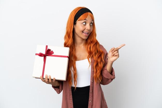 Junge frau mit orangefarbenem haar, die ein geschenk isoliert auf weißem hintergrund hält und beabsichtigt, die lösung zu realisieren, während sie einen finger hochhebt