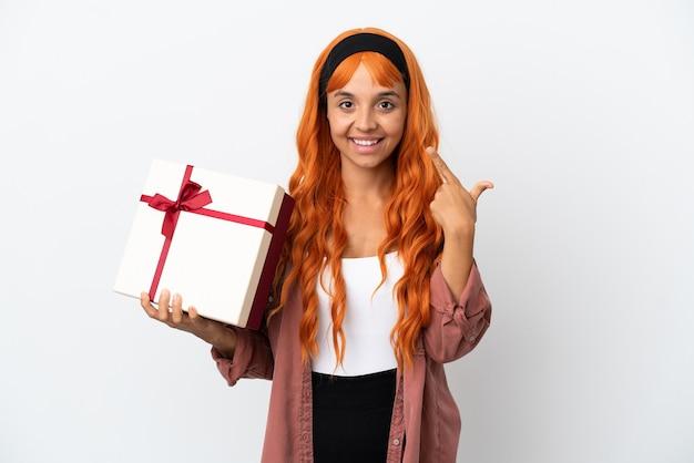 Junge frau mit orangefarbenem haar, die ein geschenk isoliert auf weißem hintergrund hält und eine geste mit dem daumen nach oben gibt