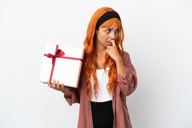 Junge frau mit orangefarbenem haar, die ein geschenk isoliert auf weißem hintergrund hält und zweifel hat