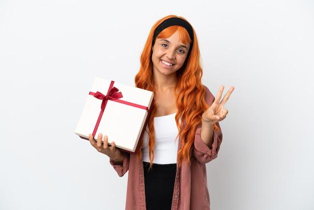 Junge frau mit orangefarbenem haar hält ein geschenk isoliert auf weißem hintergrund lächelnd und zeigt victory-zeichen