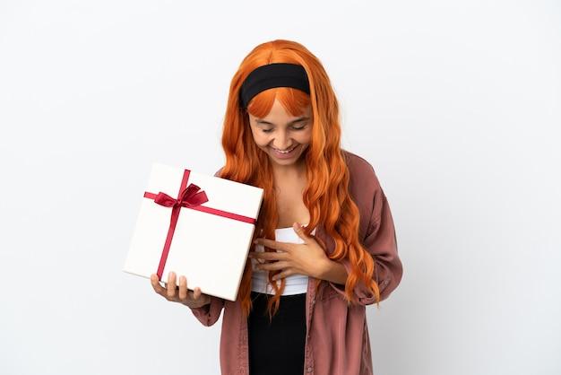 Junge frau mit orangefarbenem haar hält ein geschenk isoliert auf weißem hintergrund und lächelt viel