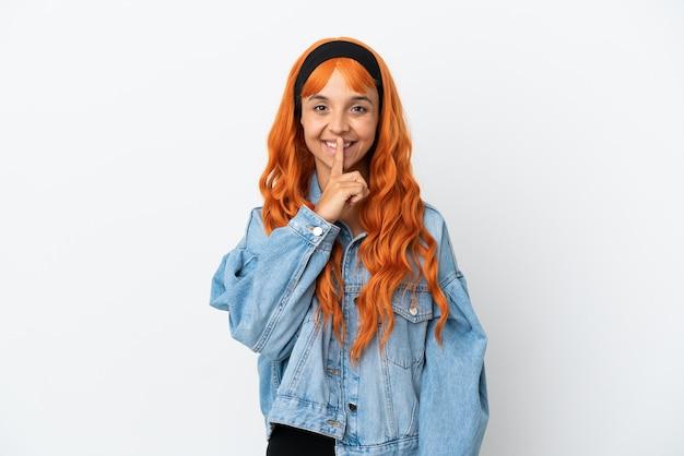 Junge frau mit orangefarbenen haaren auf weißem hintergrund, die ein zeichen der stille zeigt, geste, die finger in den mund steckt