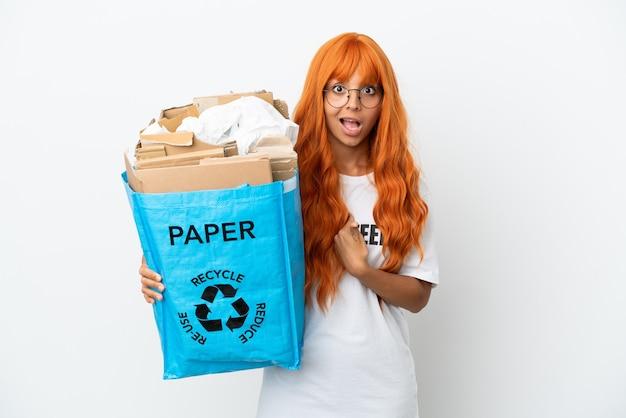 Junge frau mit orangefarbenen haaren, die eine recyclingtüte voller papier hält, die isoliert auf weißem hintergrund mit überraschendem gesichtsausdruck recycelt werden kann