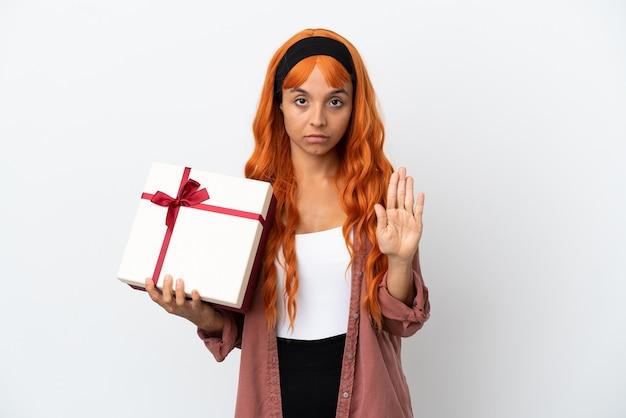 Junge frau mit orangefarbenen haaren hält ein geschenk isoliert auf weißem hintergrund und macht stoppgeste