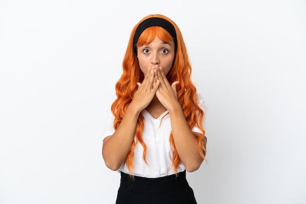 Junge frau mit orangefarbenen haaren isoliert auf weißem hintergrund, die den mund mit den händen bedeckt