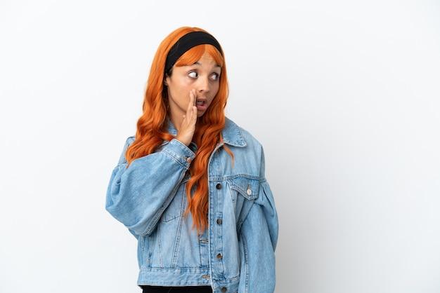 Junge frau mit orangefarbenen haaren isoliert auf weißem hintergrund, die etwas mit überraschungsgeste flüstert, während sie zur seite schaut