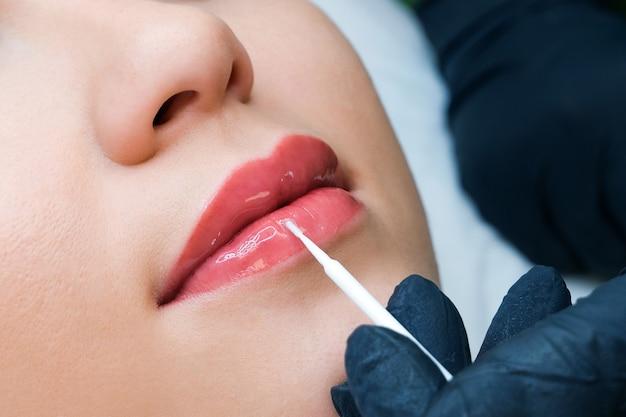 Junge frau mit permanent make-up auf den lippen im kosmetiksalon. auftragen von flüssigem glas auf die lippen