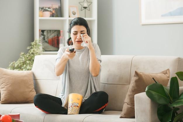 Junge frau mit popcorn-eimer hält die tv-fernbedienung zur kamera auf dem sofa hinter dem couchtisch im wohnzimmer