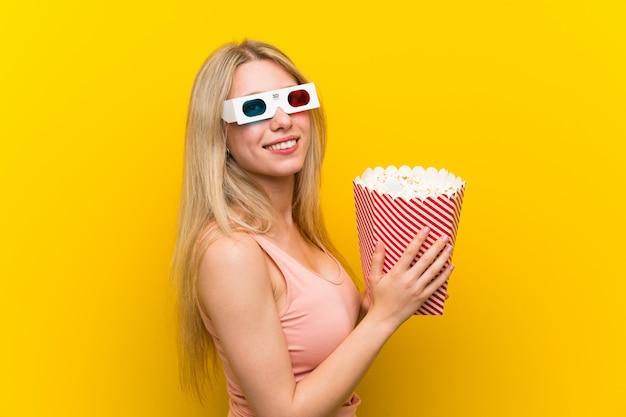 Junge frau mit popcorn über rosa wand