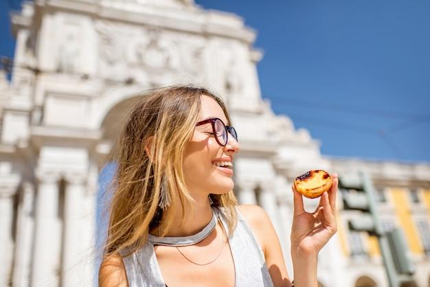 Junge frau mit portugiesischem eierkuchenteig namens pastel de nata im freien auf dem triumphbogenhintergrund in lissabon