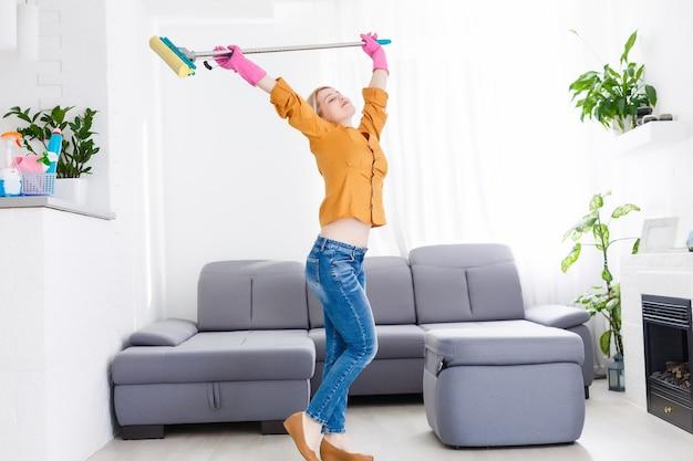 Junge frau mit putzzeug tanzt im wohnzimmer.