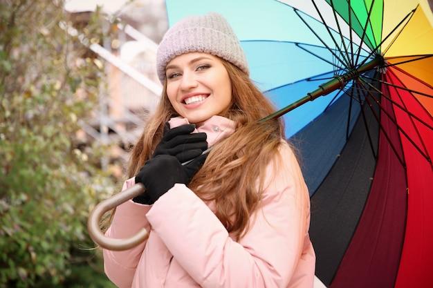 Junge frau mit regenbogenregenschirm im freien
