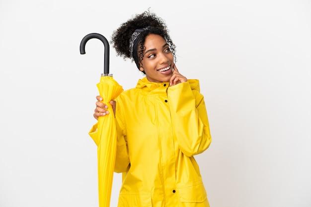 Junge frau mit regenfestem mantel und regenschirm isoliert auf weißem hintergrund denkt beim nachschlagen an eine idee