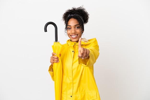 Junge frau mit regenfestem mantel und regenschirm isoliert auf weißem hintergrund, der einen finger zeigt und hebt