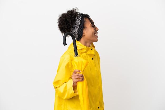 Junge frau mit regenfestem mantel und regenschirm isoliert auf weißem hintergrund lachend in seitenlage