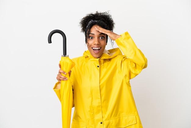 Junge frau mit regenfestem mantel und regenschirm isoliert auf weißem hintergrund mit überraschungsausdruck