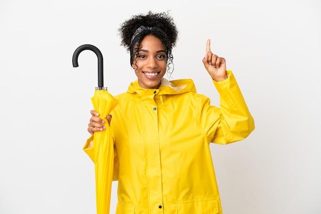 Junge frau mit regenfestem mantel und regenschirm isoliert auf weißem hintergrund zeigt eine großartige idee