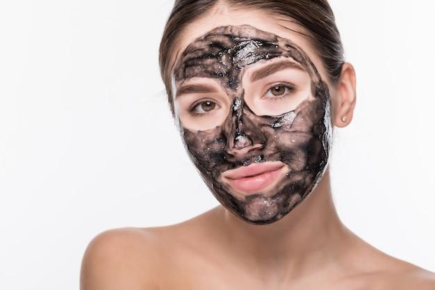 Junge frau mit reinigender schwarzer maske auf ihrem gesicht lokalisiert auf weißer wand