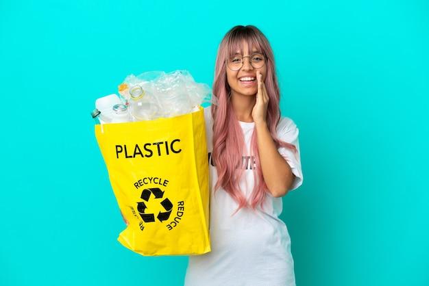 Junge frau mit rosa haaren, die eine tasche voller plastikflaschen zum recycling hält, isoliert auf blauem hintergrund, die mit weit geöffnetem mund schreit