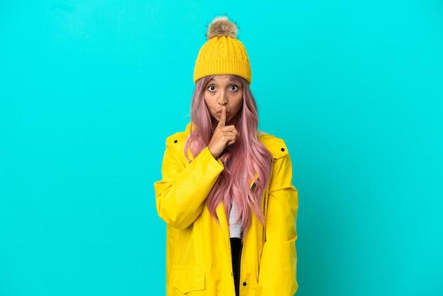 Junge frau mit rosa haaren, die einen regendichten mantel trägt, der auf blauem hintergrund isoliert ist und ein zeichen der stille zeigt, die den finger in den mund steckt